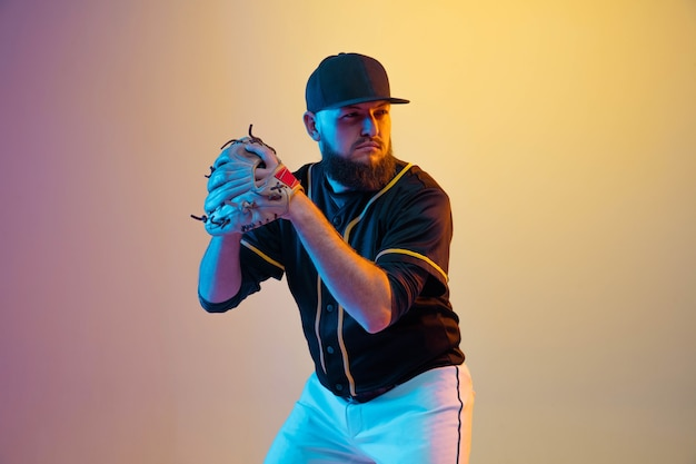 Бейсболист, питчер в черной форме тренируется и тренируется на градиентной стене в неоновом свете. молодой профессиональный спортсмен в действии и движении. здоровый образ жизни, спорт, концепция движения.
