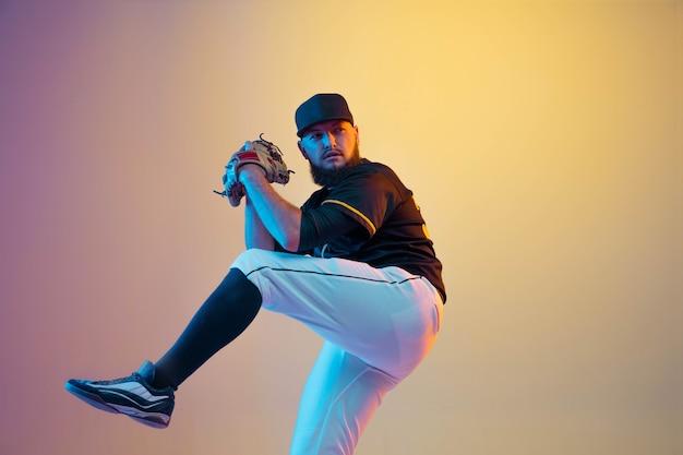 야구 선수, 네온 불빛에 그라데이션 벽에 검은 제복을 입은 투수 연습 및 훈련. 행동과 움직임에 젊은 전문 운동가. 건강한 라이프 스타일, 스포츠, 운동 개념.