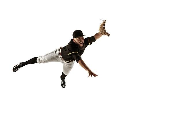 Питчер бейсболиста в черной форме тренируется на белой стене