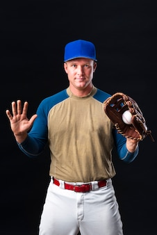 Baseball player with cap posing with glove