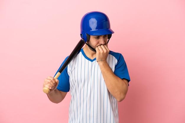 Бейсболист со шлемом и битой, изолированные на розовом фоне, сомневаясь