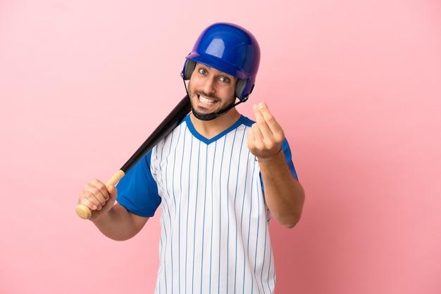 お金のジェスチャーを作るピンクの背景に分離されたヘルメットとバットを持つ野球選手