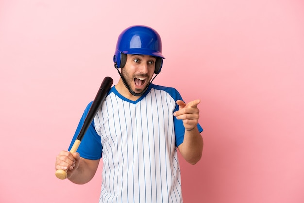 Бейсболист со шлемом и битой, изолированные на розовом фоне, указывая пальцем в сторону и представляя продукт