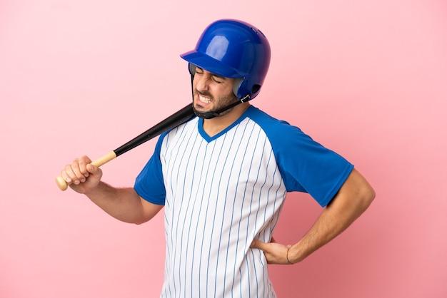 努力をしたために腰痛に苦しんでいるピンクの背景に分離されたヘルメットとバットを持つ野球選手