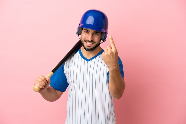 Baseball player with helmet and bat isolated on pink background doing coming gesture