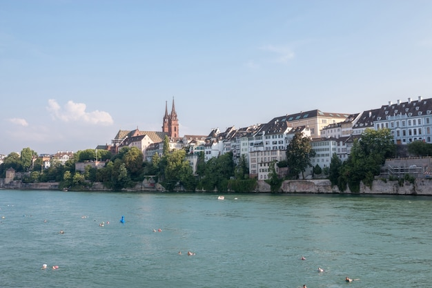 Basel, switzerland - june 23, 2017: view on basel city and river rhine, switzerland, europe. people swim in water. summer landscape, sunshine weather, blue sky and sunny day