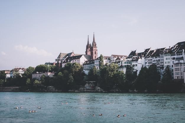 Базель, швейцария - 23 июня 2017: вид на город базель и реку рейн, швейцария, европа. люди плавают в воде. летний пейзаж, солнечная погода, голубое небо и солнечный день
