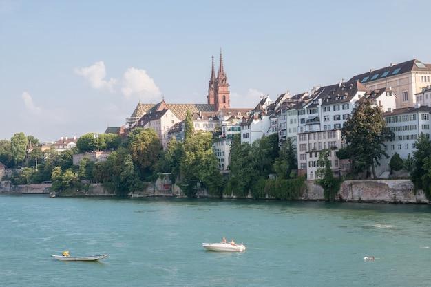 바젤, 스위스 - 2017년 6월 23일: 바젤 도시와 라인강, 스위스, 유럽에서 볼 수 있습니다. 사람들은 물에서 수영합니다. 여름 풍경, 햇살 날씨, 푸른 하늘과 화창한 날