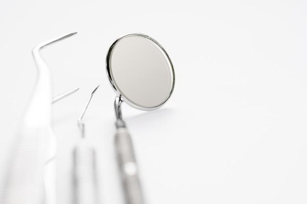 白い背景の上の基本的な歯科医のツール。