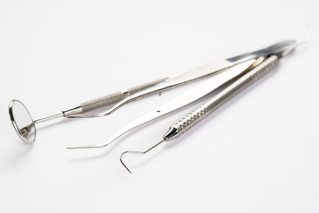 Basic dentist tools on white background.