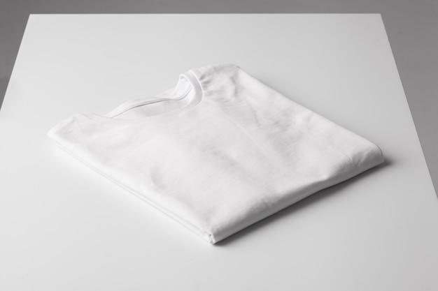 灰色のテーブルの基本的な折り畳まれた白いtシャツは、tシャツのブランド化のためにモックアップします