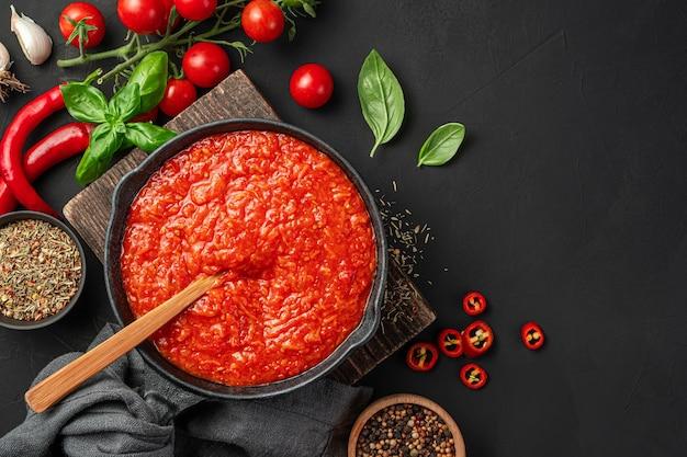 材料と黒の背景にバジルとコショウと基本的なイタリアのトマトソース。マリナラソース。上面図、コピースペース。