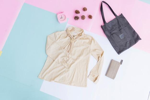 Базовый макет женской одежды, рубашка на бледно-мятном пастельном фоне. концепция образа жизни. будильник. кошелек. сумка