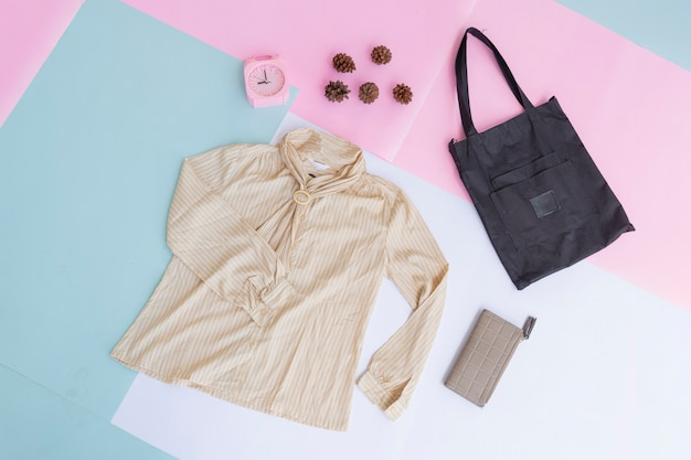 Basic layout of women's clothing, shirt on pale mint pastel background. lifestyle concept. alarm clock. purse. bag