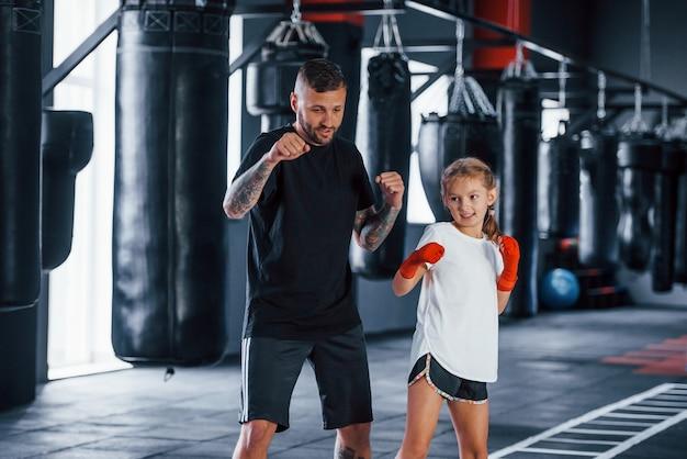 Основные удары. молодой татуированный тренер по боксу учит милую девочку в тренажерном зале.