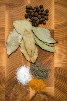 Basic spices and herbs still life on wooden cutting board.