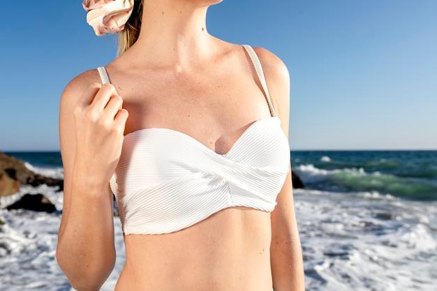Top bikini bianco di base primo piano di costumi da bagno in spiaggia