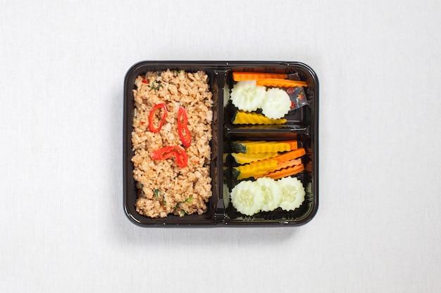 Жареный рис с базиликом и куриным фаршем, положить в черный пластиковый ящик, положить на белую скатерть, пищевой ящик, жареный цыпленок с базиликом в остром соусе, тайская кухня.