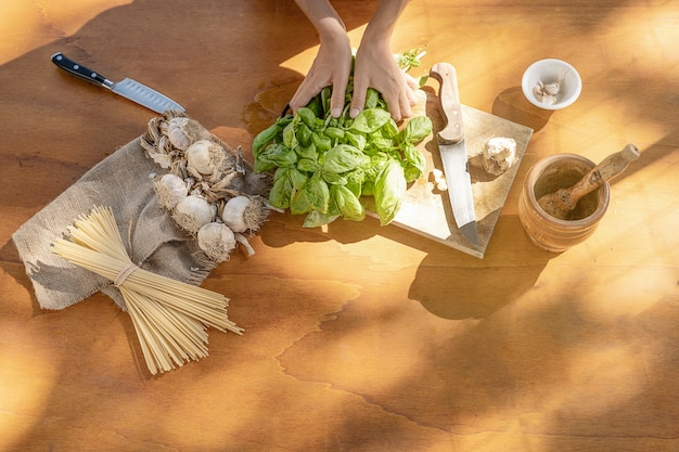 Basil garlic spaghetti and mortar on wooden background top view