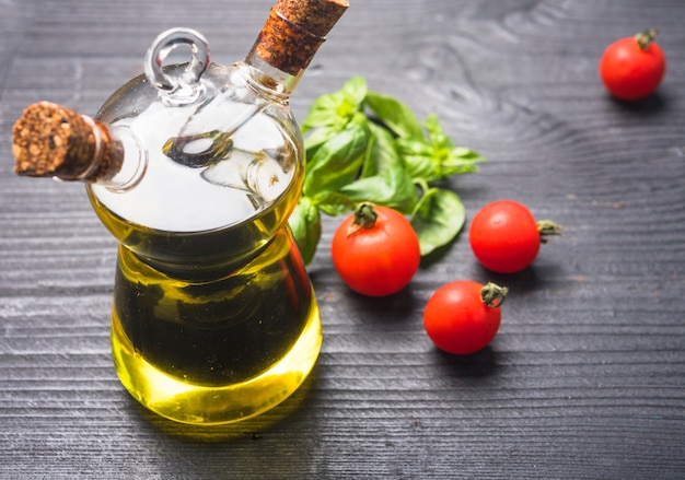 Basil leaves; tomatoes and bottle of olive oil with cork stopper