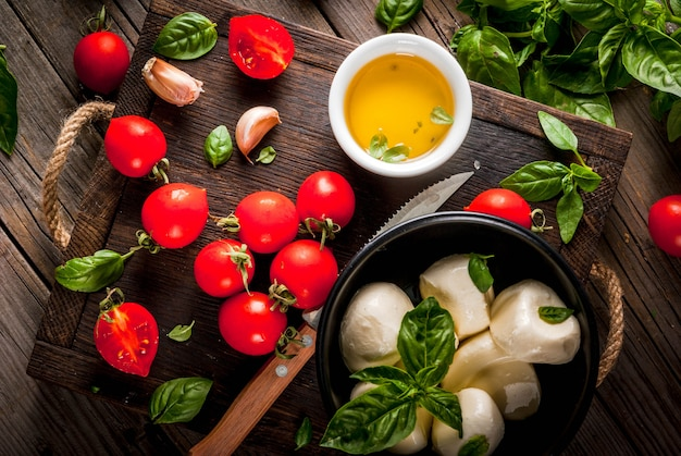 Basil, tomatoes, mozzarella cheese, olive oil on an old wooden table