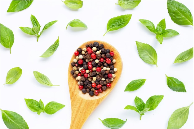 Basil with red, white and black peppercorns with wooden spoon