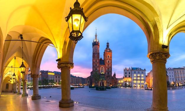 ポーランド、クラクフの日没時にクラクフ織物会館から見た中世の中央市場広場にある聖マリア大聖堂