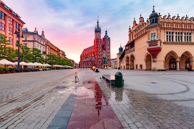 クラクフの日の出の旧市街にある中世のメインマーケット広場にある聖マリア大聖堂