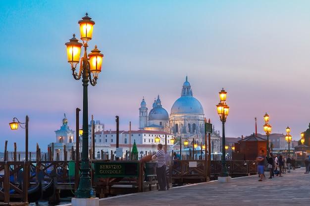 Базилика санта-мария-делла-салюте и набережная гондолы ночью, венеция, италия