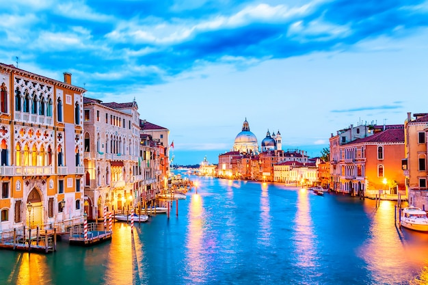 Basilica santa maria della salute and grand canal at blue hour sunset in venice, italy with boats and reflections.
