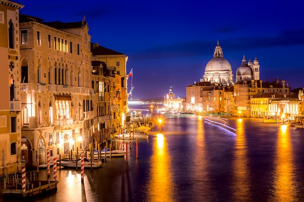 Basilica santa maria della salute, punta della dogona and grand canal at blue hour sunset in venice, italy with reflections