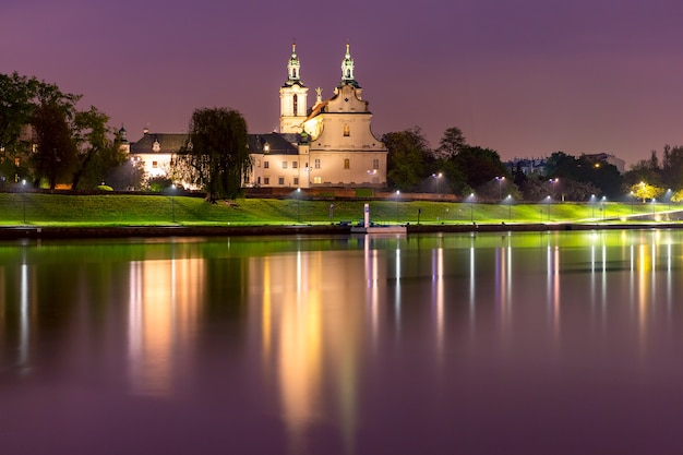 Basilica of st michael the archangel with reflection in the river at night, krakow