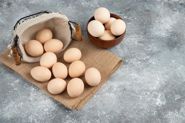 Корзина и миска, полная органических свежих сырых яиц на мраморной поверхности.