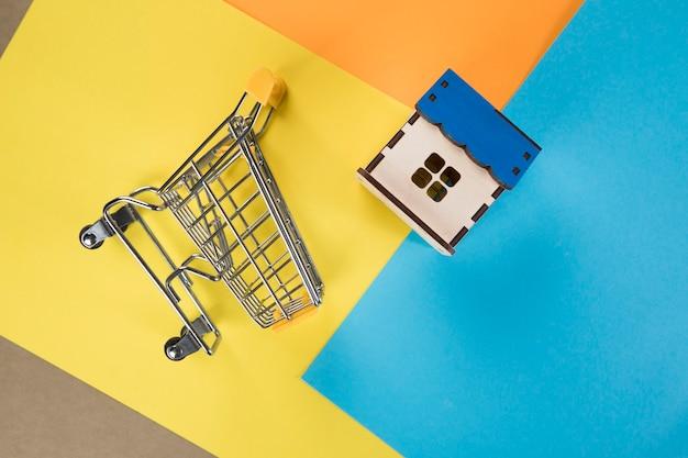 バスケットと家。住宅購入のコンセプト。色付きの紙に