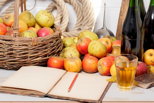 Basket of apples, bottles of cider and old notebook