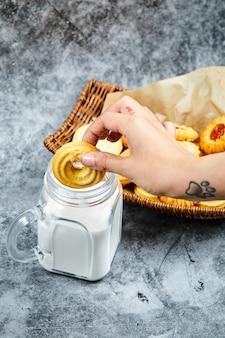 Cesto di biscotti assortiti, latte e mano che tiene un biscotto.