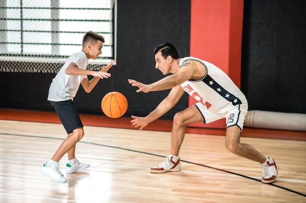 농구. 체육관에서 청소년을 훈련하는 검은 머리 남자