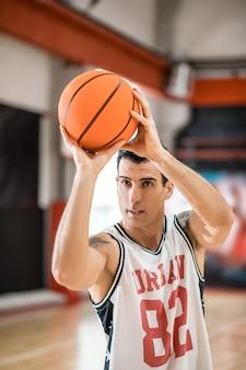 농구 선수. 반지에 공을 던지는 문신과 젊은 남자