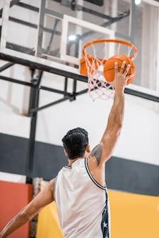 농구. sportman 바구니에 공을 던지는