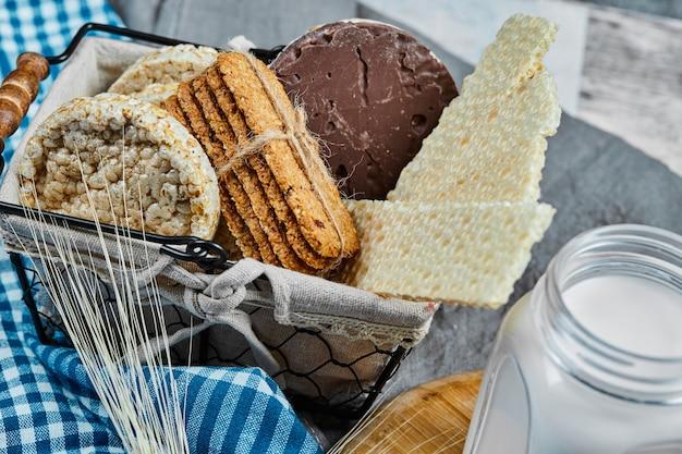 Cesto di biscotti e un barattolo di latte su un tavolo di marmo, primi piani.