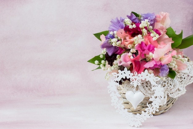 In the basket a bouquet of sweet peas and lilies of the valley