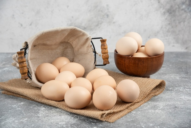 Basket and bowl full of organic fresh uncooked eggs on marble surface.