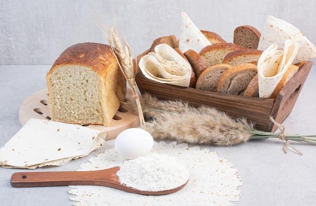 Cesto di pane e lavash sul tavolo con uova e farina