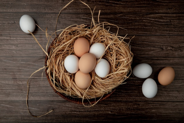 Basket of eggs in nest with eggs around on wooden table