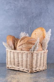 Корзина, заполненная хлебами и стеблями ковыля на мраморной поверхности