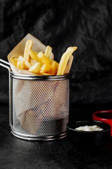Cesto di patatine fritte servito con maionese
