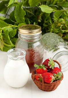 Basket of fresh strawberries with milk and honey