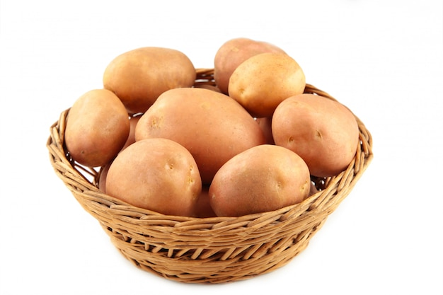 Basket of fresh tasty new potatoes isolated on white background. top view
