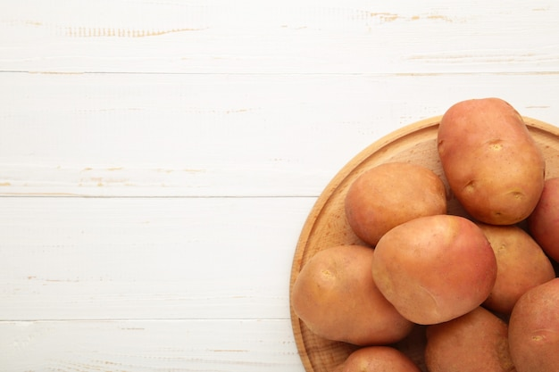 Basket of fresh tasty new potatoes on white background. top view