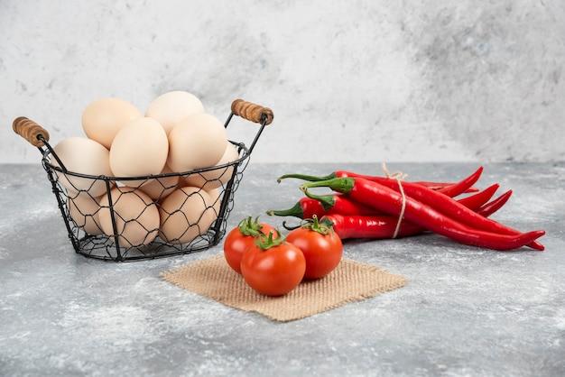 Cesto di uova crude fresche, peperoncino e pomodori su marmo.